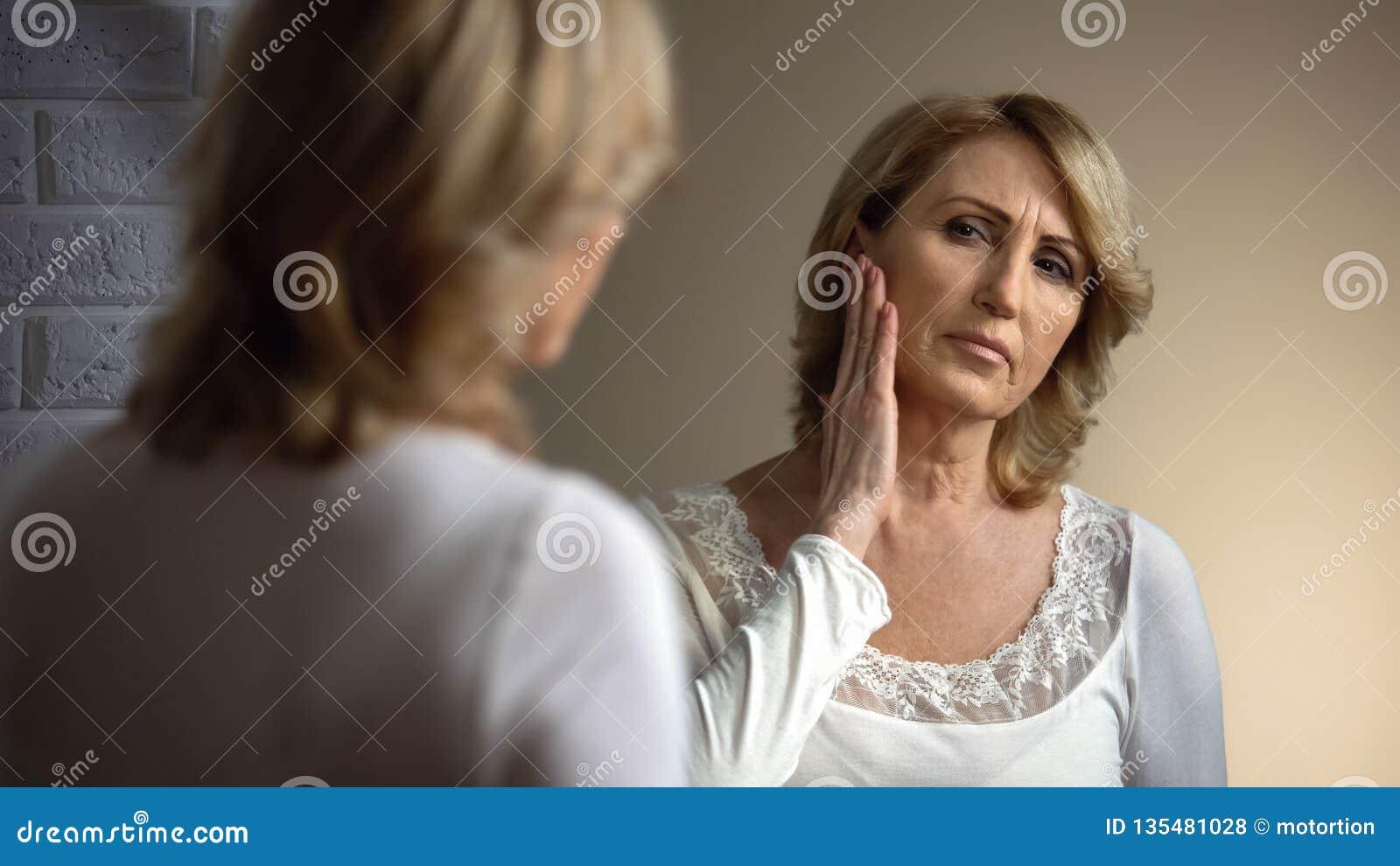 Donna anziana deprimente che guarda in specchio, toccante fronte corrugato, bellezza persa