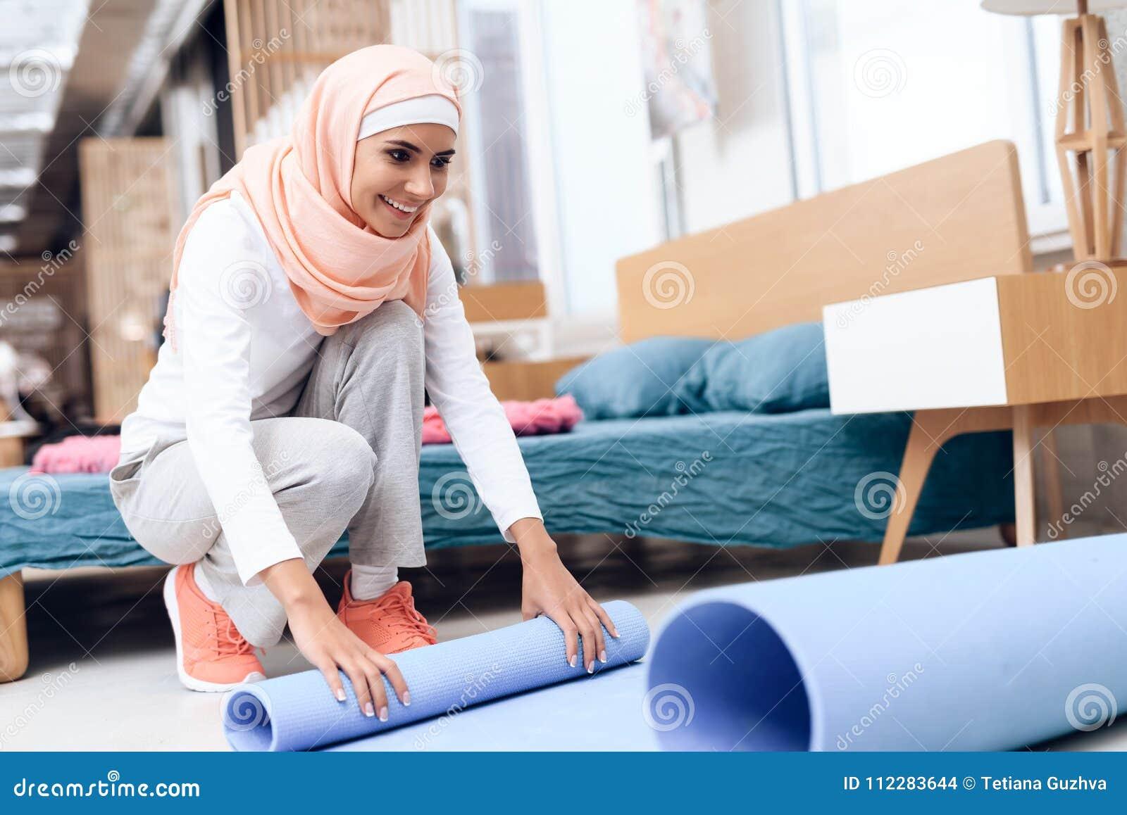 Donna araba che prepara una stuoia per fare ginnastica nella camera da letto