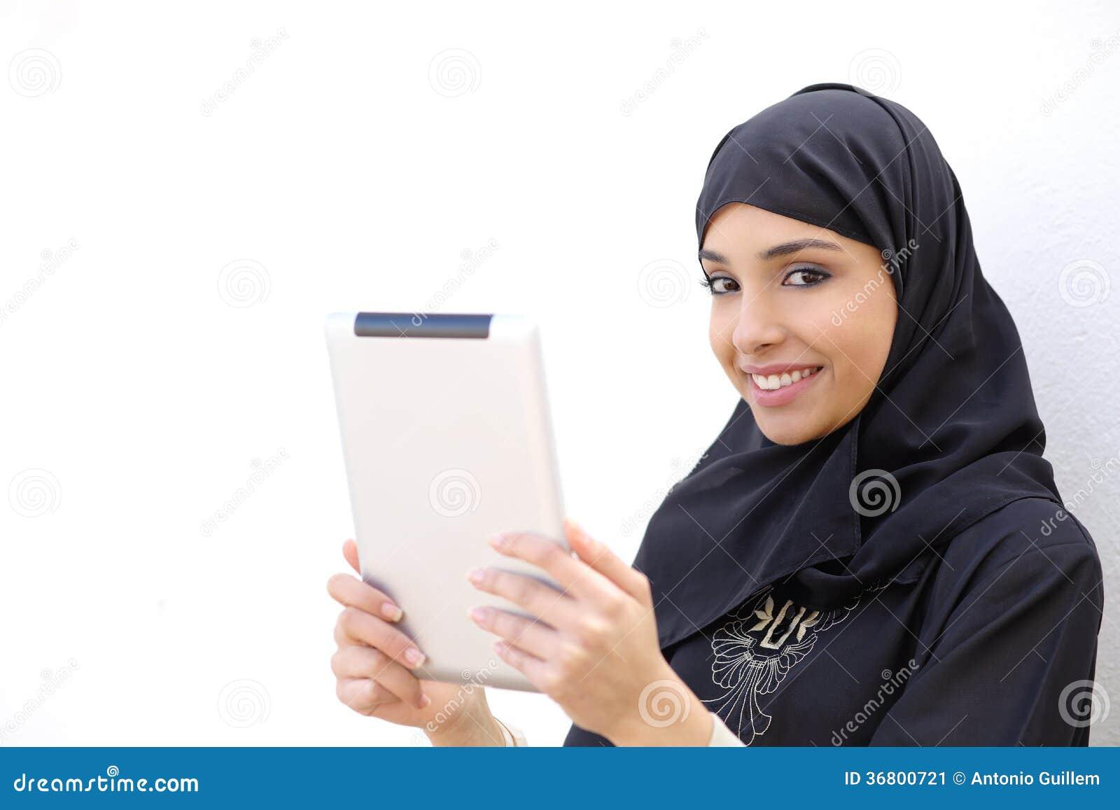 Donna araba che tiene una compressa e che esamina macchina fotografica