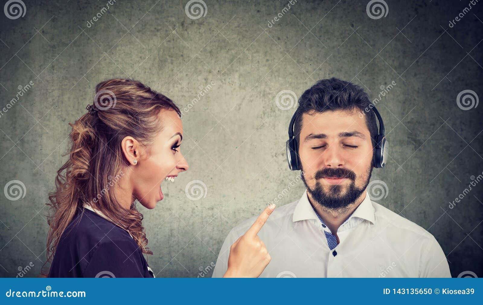Donna arrabbiata che urla ad un marito calmo che ascolta la musica