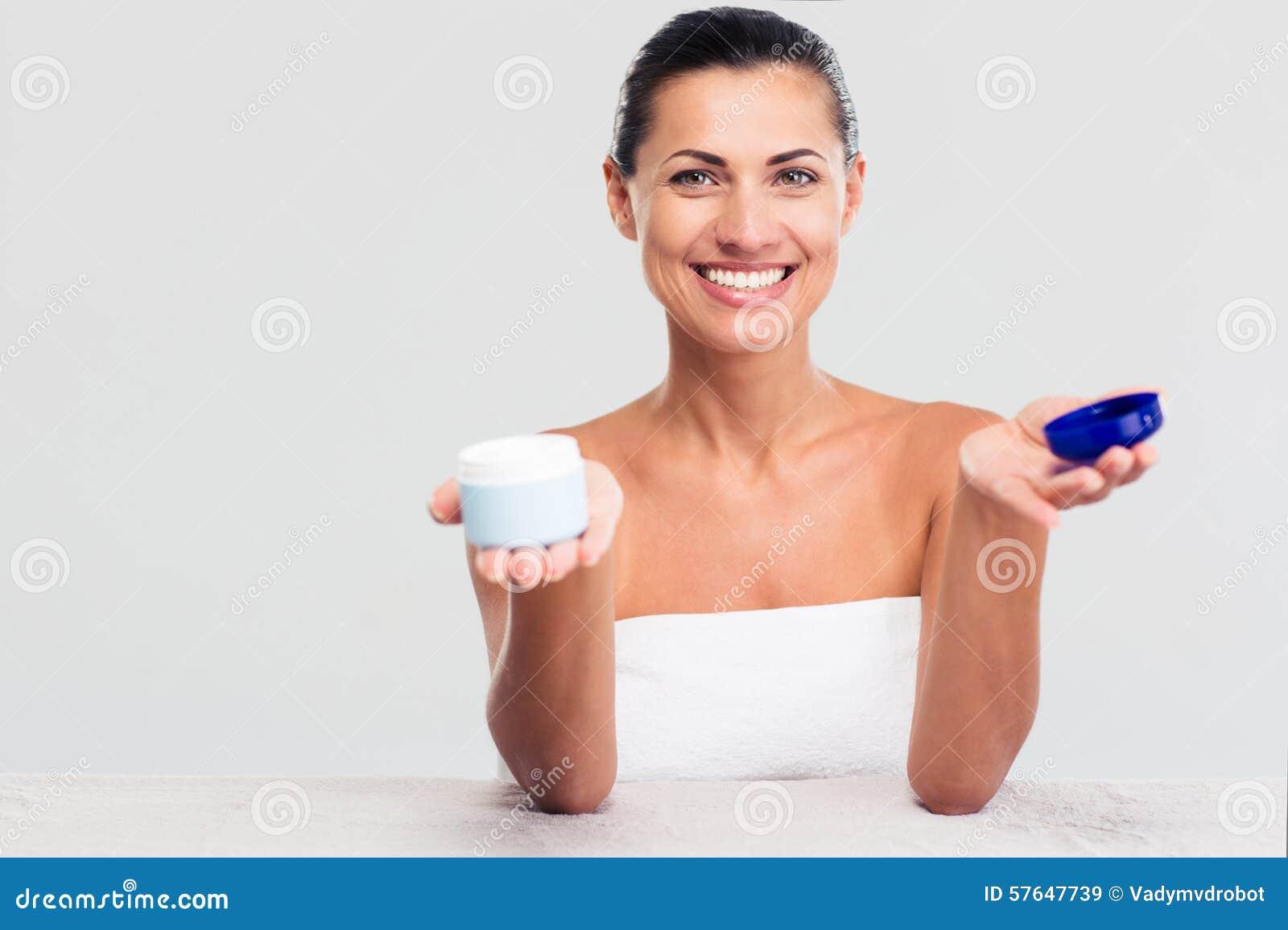 Donna in asciugamano che si siede alla tavola e che tiene barattolo crema