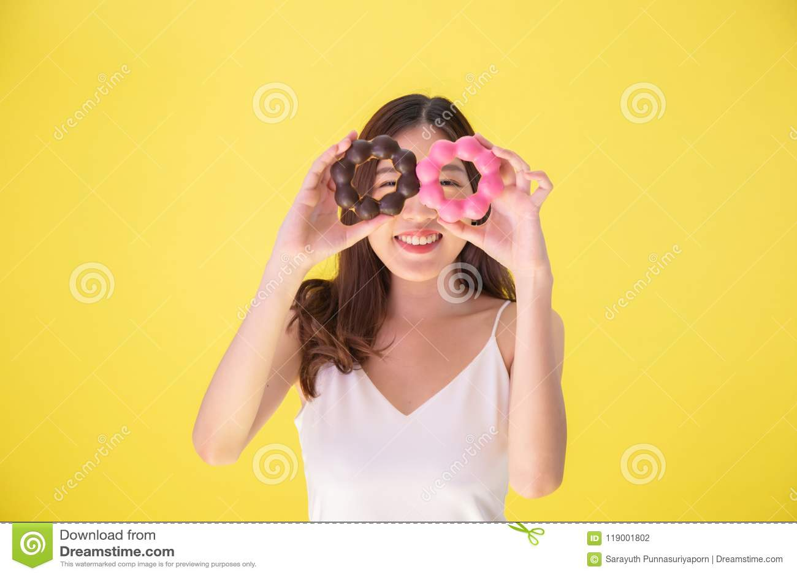Donna asiatica attraente che tiene due guarnizioni di gomma piuma con l espressione sorridente sveglia sopra fondo giallo