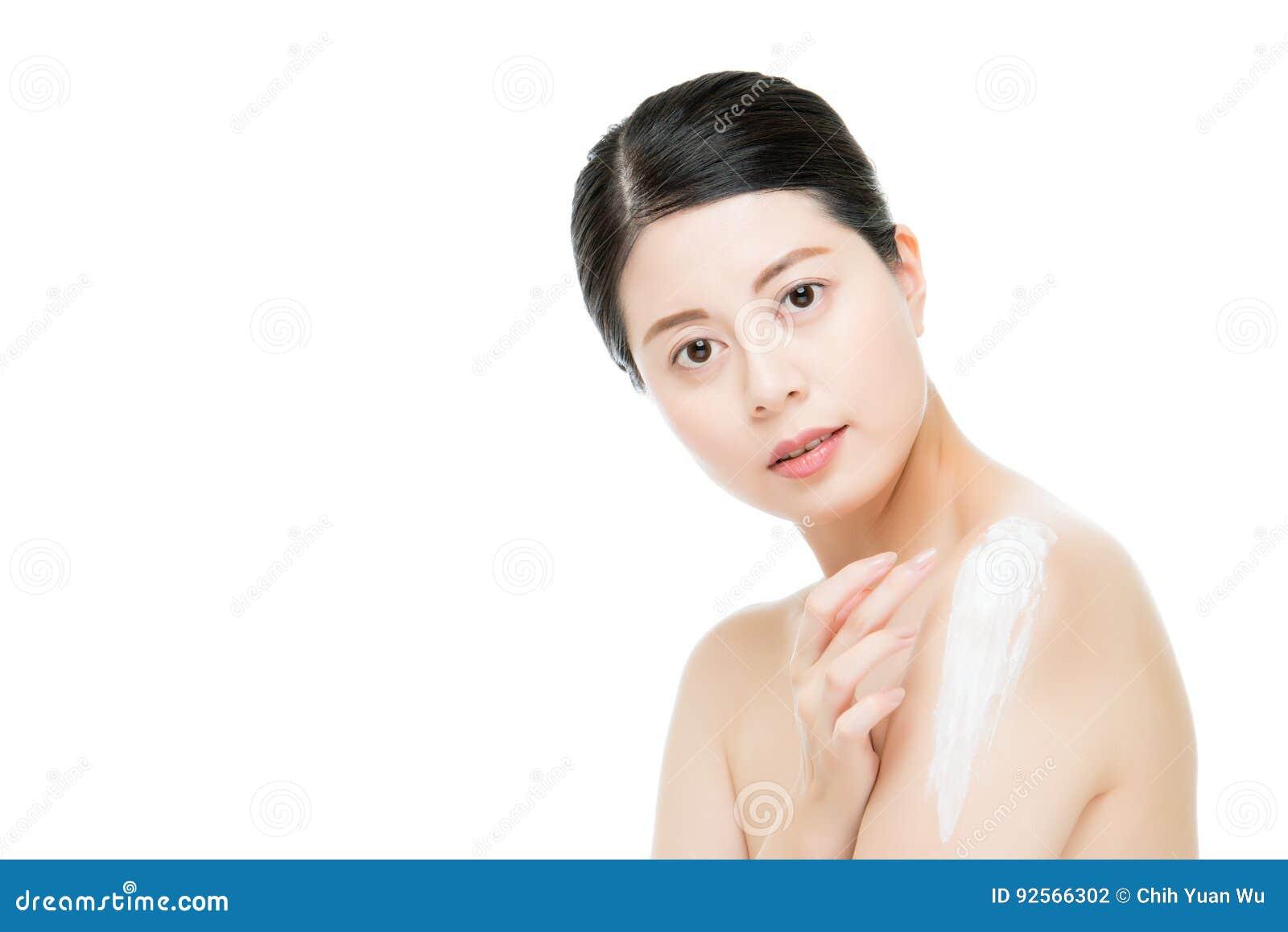 Donna asiatica che applica crema d idratazione