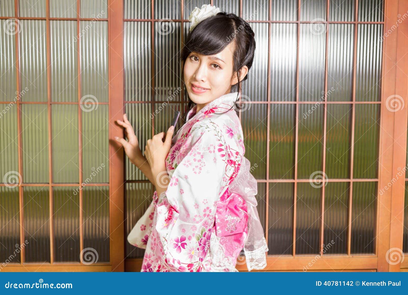 Donna asiatica che porta un kimono davanti alle finestre for Finestre di legno
