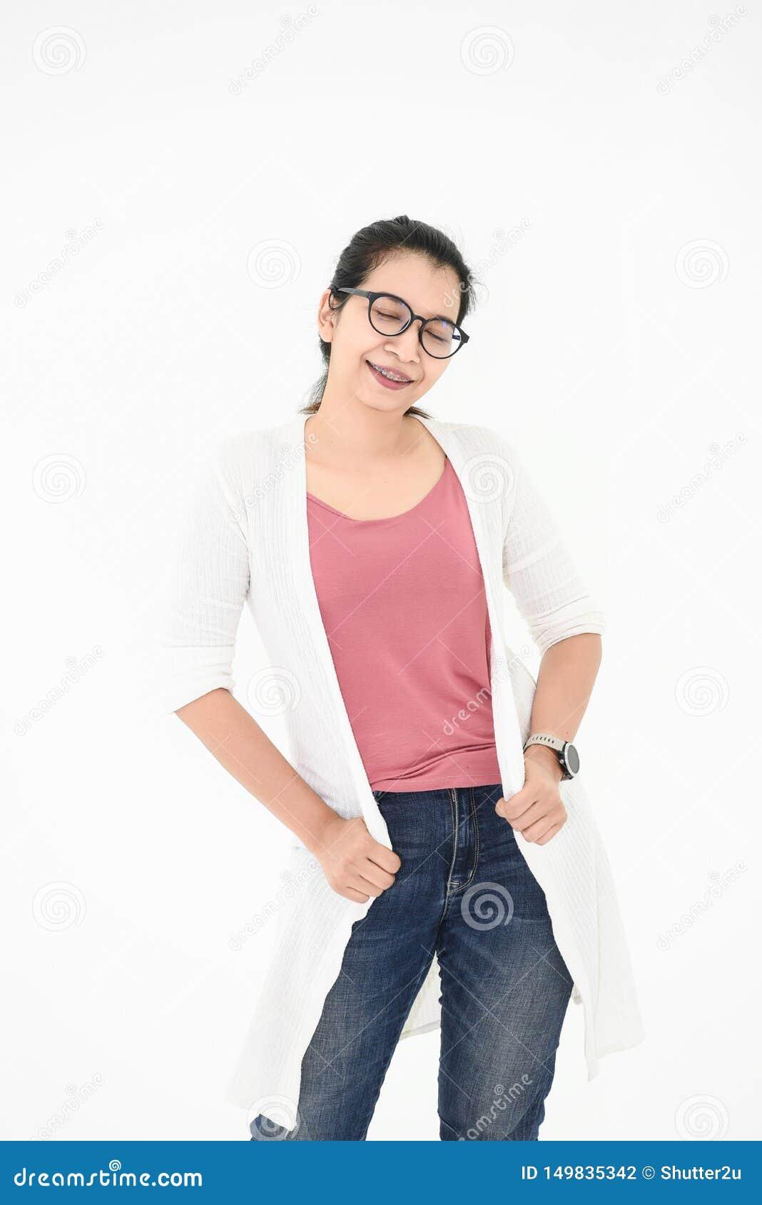 Donna asiatica che posa con l attrezzatura e gli occhiali casuali nell umore felice su fondo isolato bianco Gli occhi chiusi adat