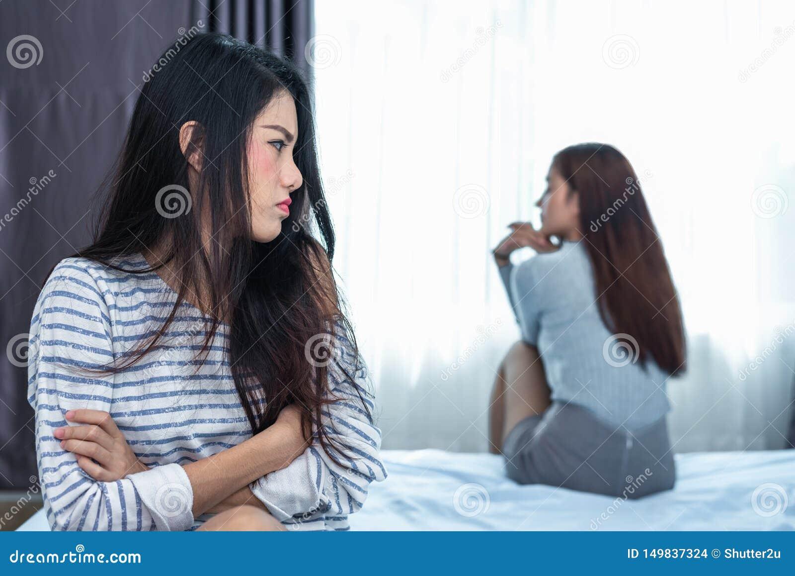 Donna asiatica che sollecita dopo il conflitto con l amica in camera da letto Gente di pensiero seria e negativa Ribaltamento ed