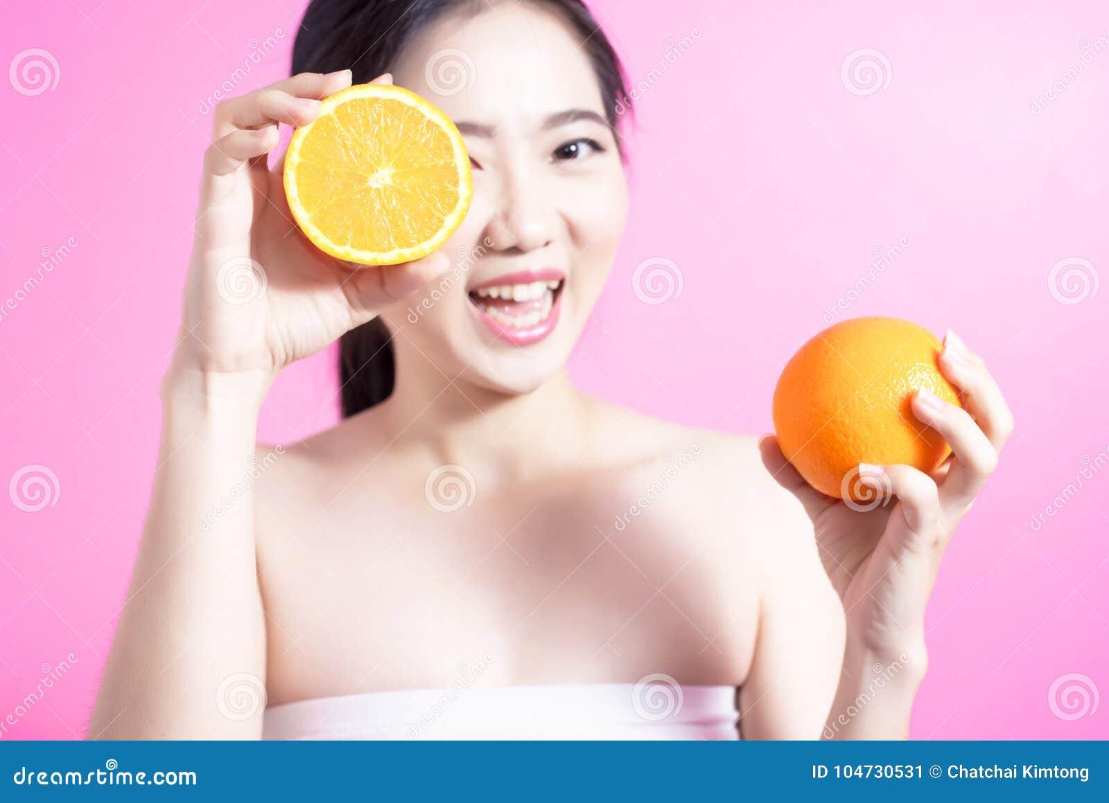 Donna asiatica con il concetto arancio Lei che sorride e che tiene arancia Fronte di bellezza e trucco naturale Isolato sopra fon
