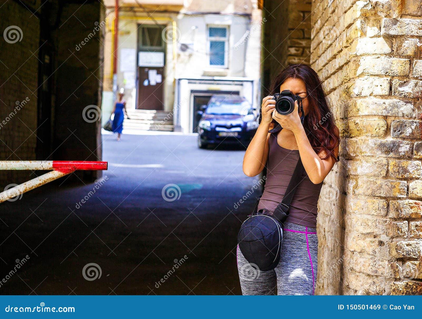 Donna asiatica del bello viaggiatore felice con la macchina fotografica Le giovani donne asiatiche allegre che usando la macchina
