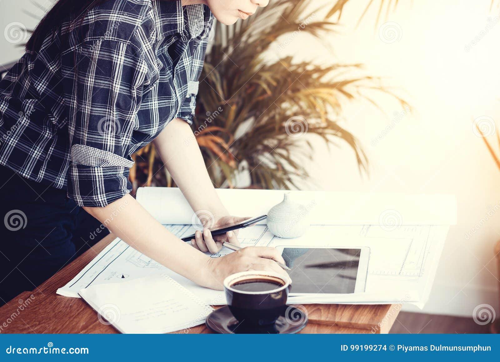 Donna asiatica dell architetto che lavora a casa con la compressa ed i modelli