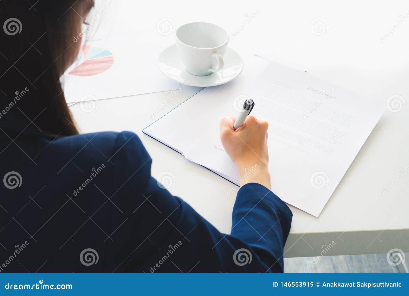 Donna asiatica di affari che scrive firma nel documento