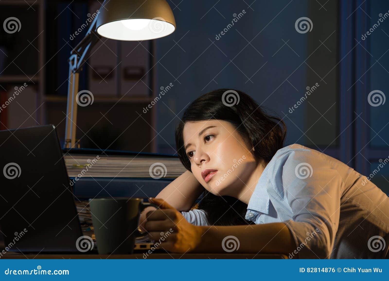 Donna asiatica di affari sonnolenta lavorando fuori orario a tarda notte