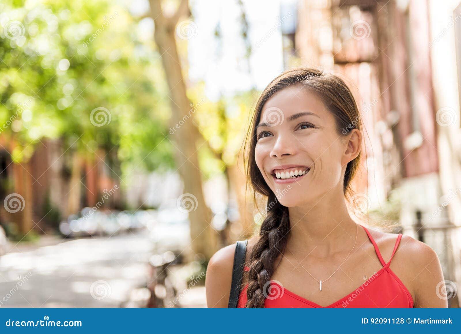 Donna asiatica felice che cammina in via soleggiata della città
