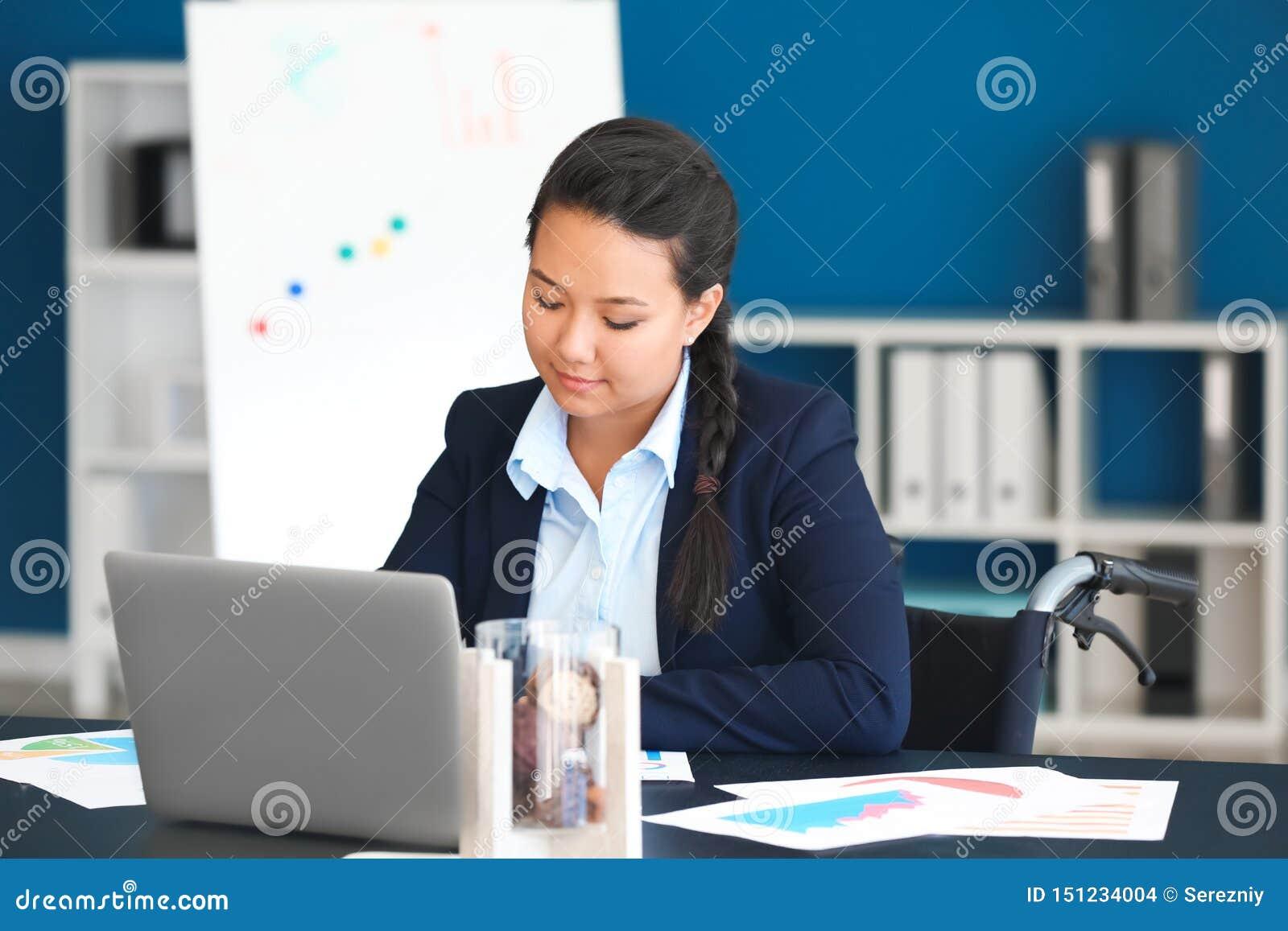 Donna asiatica nel funzionamento della sedia a rotelle con i documenti in ufficio
