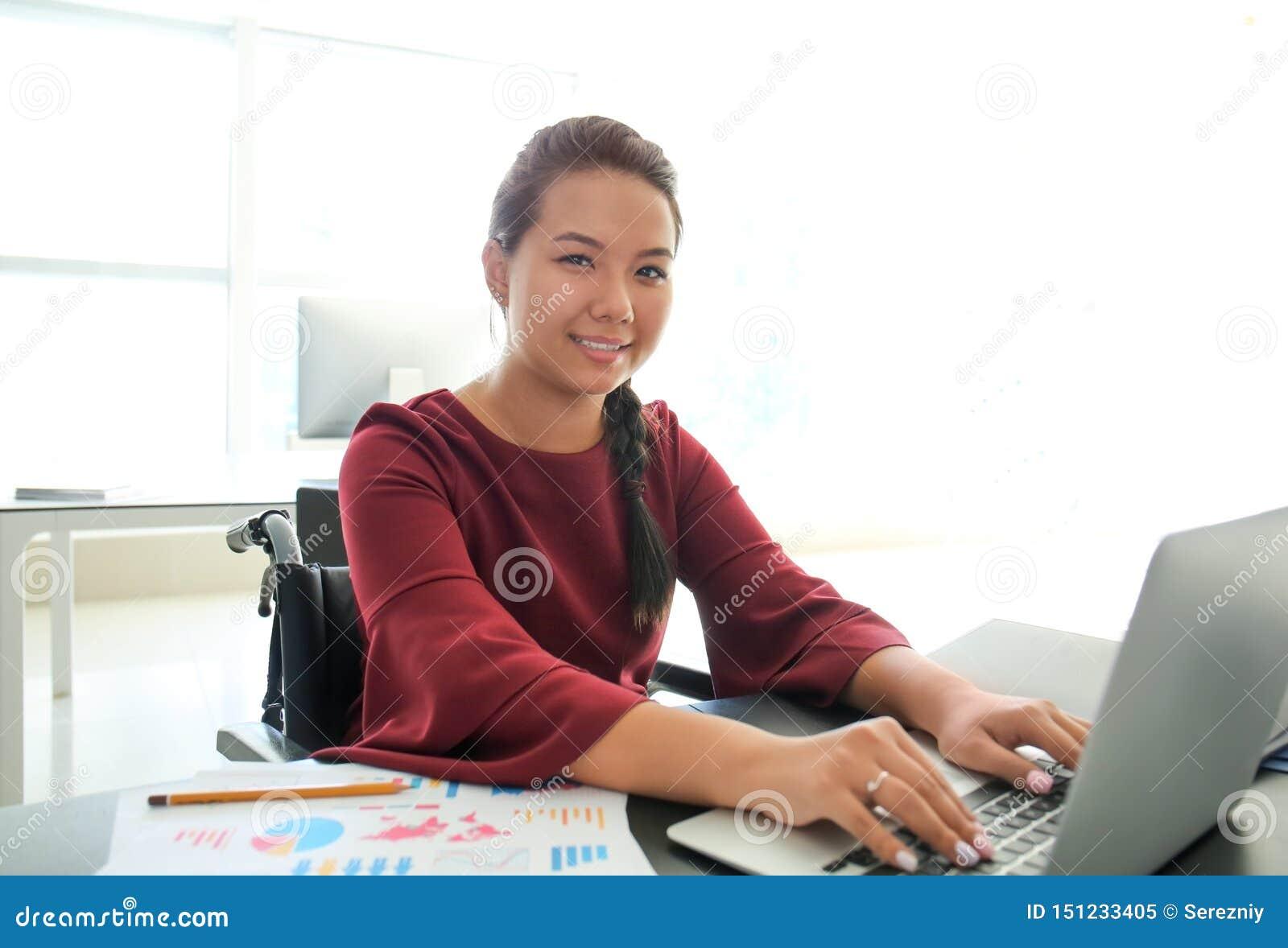 Donna asiatica nel funzionamento della sedia a rotelle con il computer portatile in ufficio