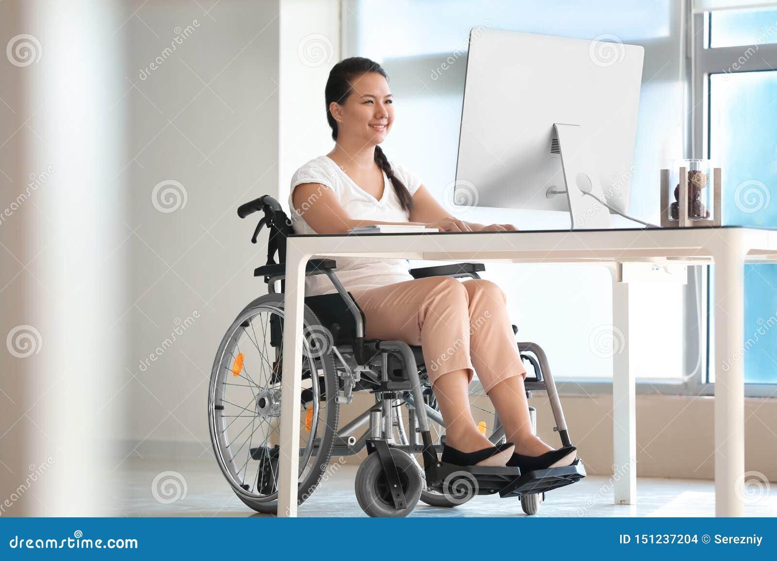 Donna asiatica nel funzionamento della sedia a rotelle con il computer in ufficio