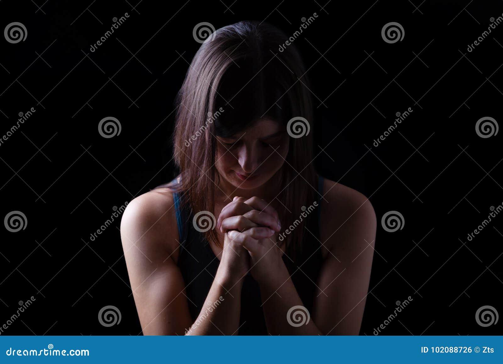 Donna atletica fedele che prega, con le mani piegate nel culto al dio