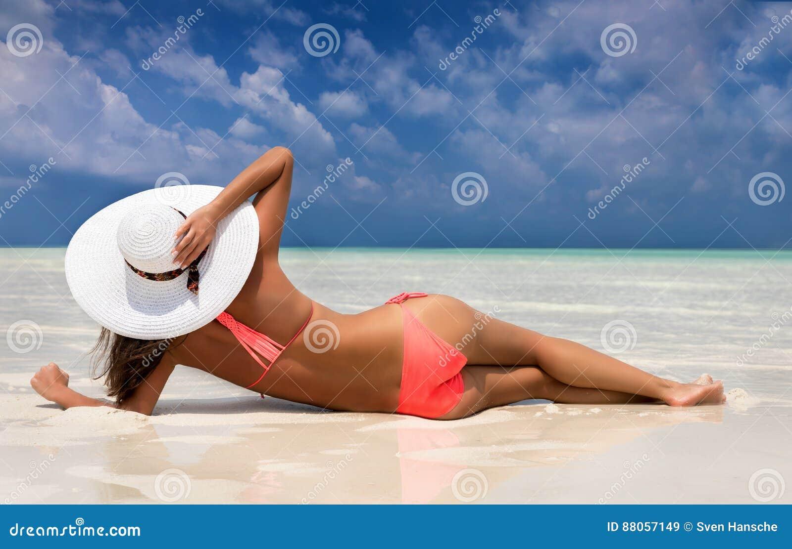 Donna attraente in bikini che si trova su una spiaggia