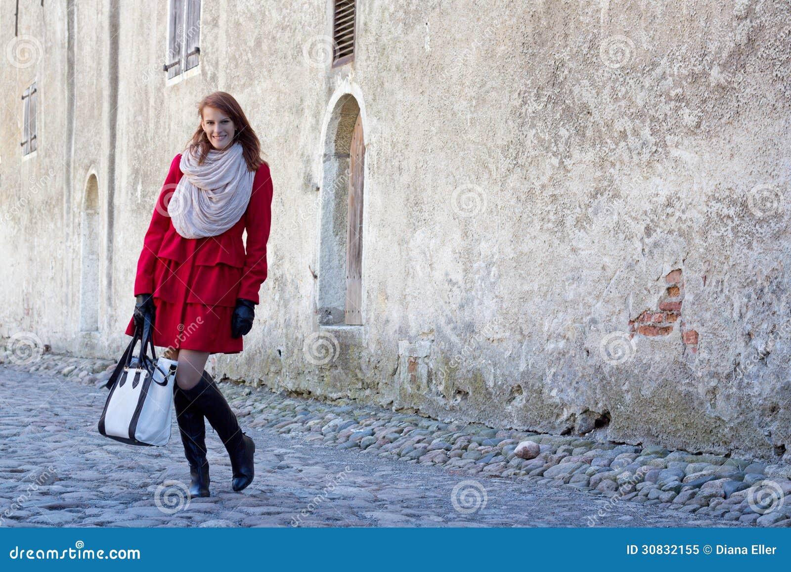 Donna attraente che controlla vecchia parete a Tallinn