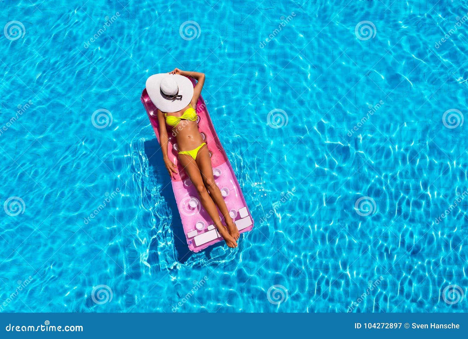 Donna attraente nello stagno con un materasso di galleggiamento