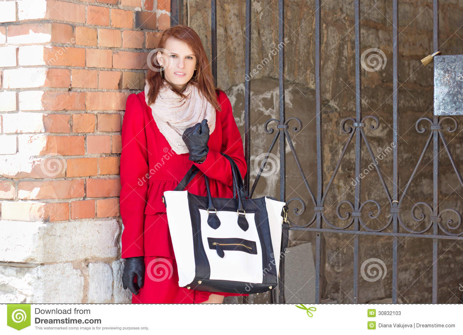 Donna attraente sopra il muro di mattoni rosso