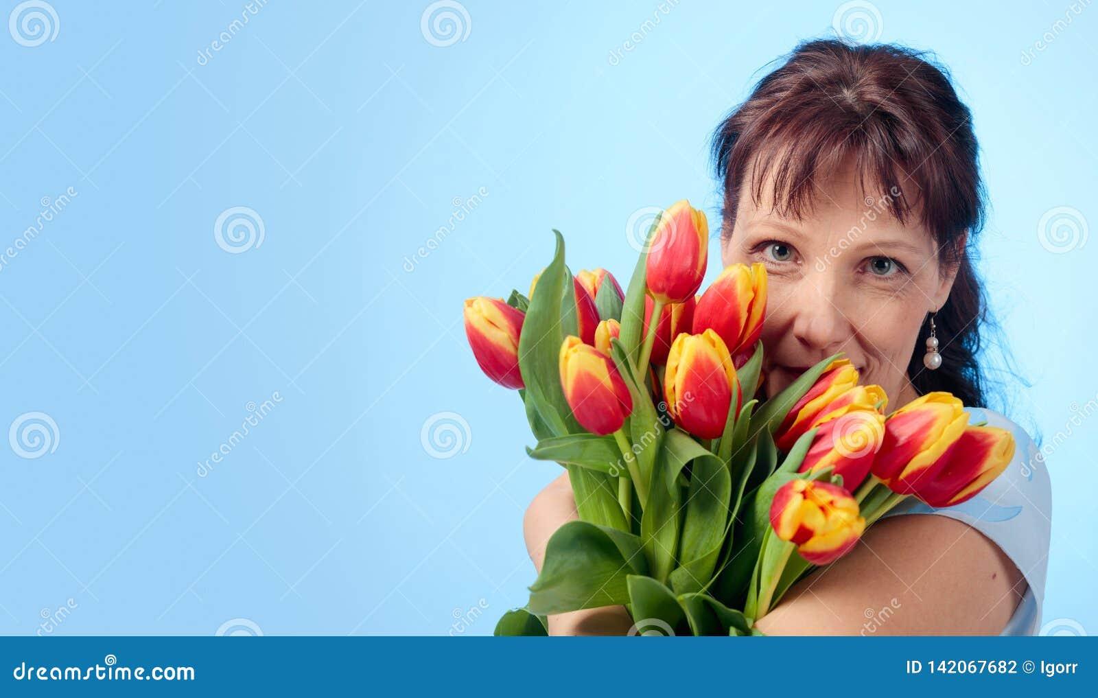 Donna attraente in vestito blu con un mazzo dei tulipani rossi e gialli