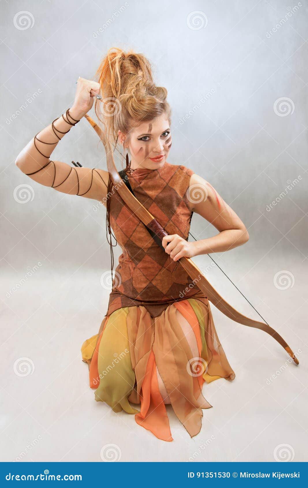 Donna in attrezzatura arancio e marrone, guerriero, modo, studio