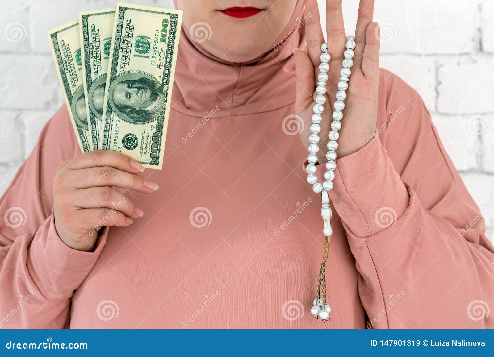Donna bianca con gli occhi azzurri in un hijab rosa che tiene un rosario ed i dollari su un fondo bianco