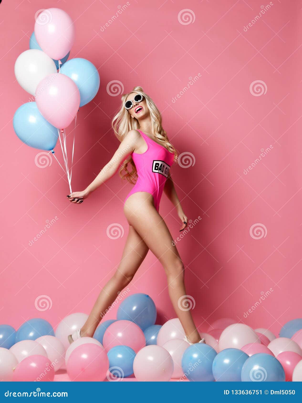 Donna bionda allegra d avanguardia sulla festa di compleanno divertendosi camminata con gli aerostati di colore pastello