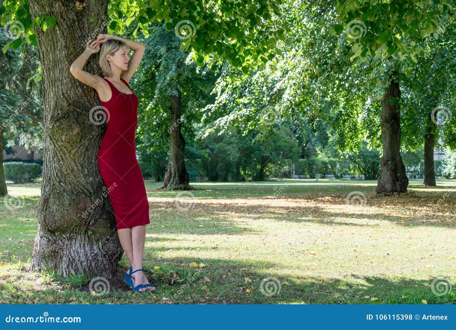 Donna bionda che abbraccia un albero in parco Ragazza in un vestito rosso che riposa in natura, pesa contro un albero