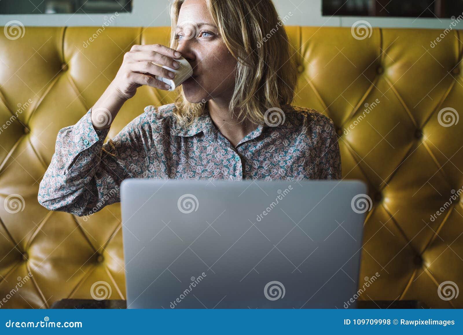 Donna bionda che lavora al suo computer portatile ad un caffè