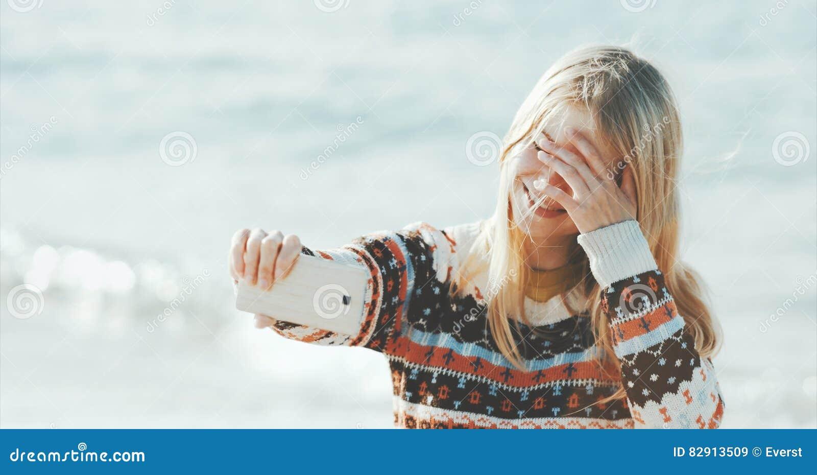Donna bionda che prende selfie facendo uso di Smartphone in mare
