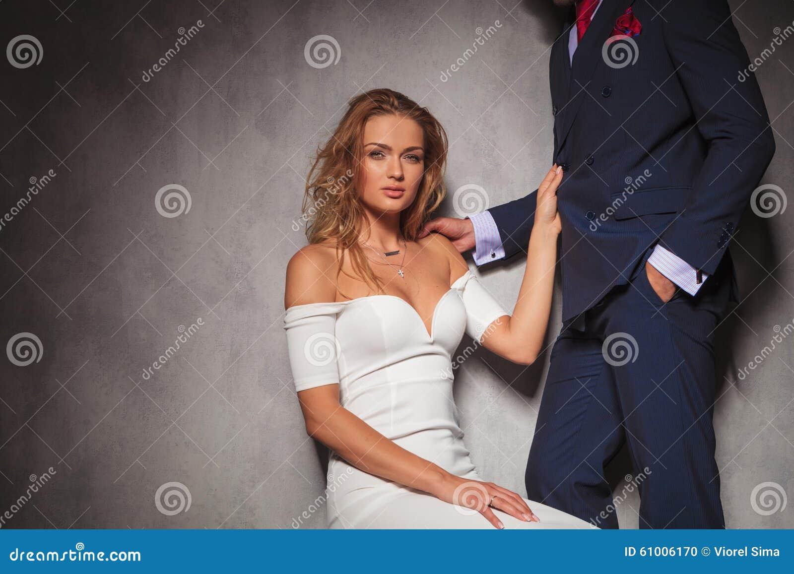 Donna bionda sexy che tiene il suo amante dal suo vestito