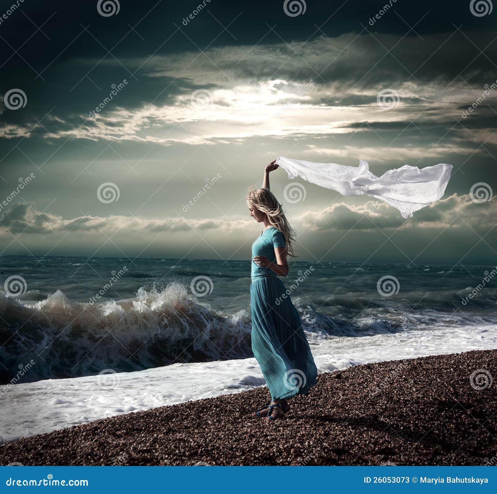 5d05c859cde6 Foto scura della donna bionda con la sciarpa bianca al mare tempestoso