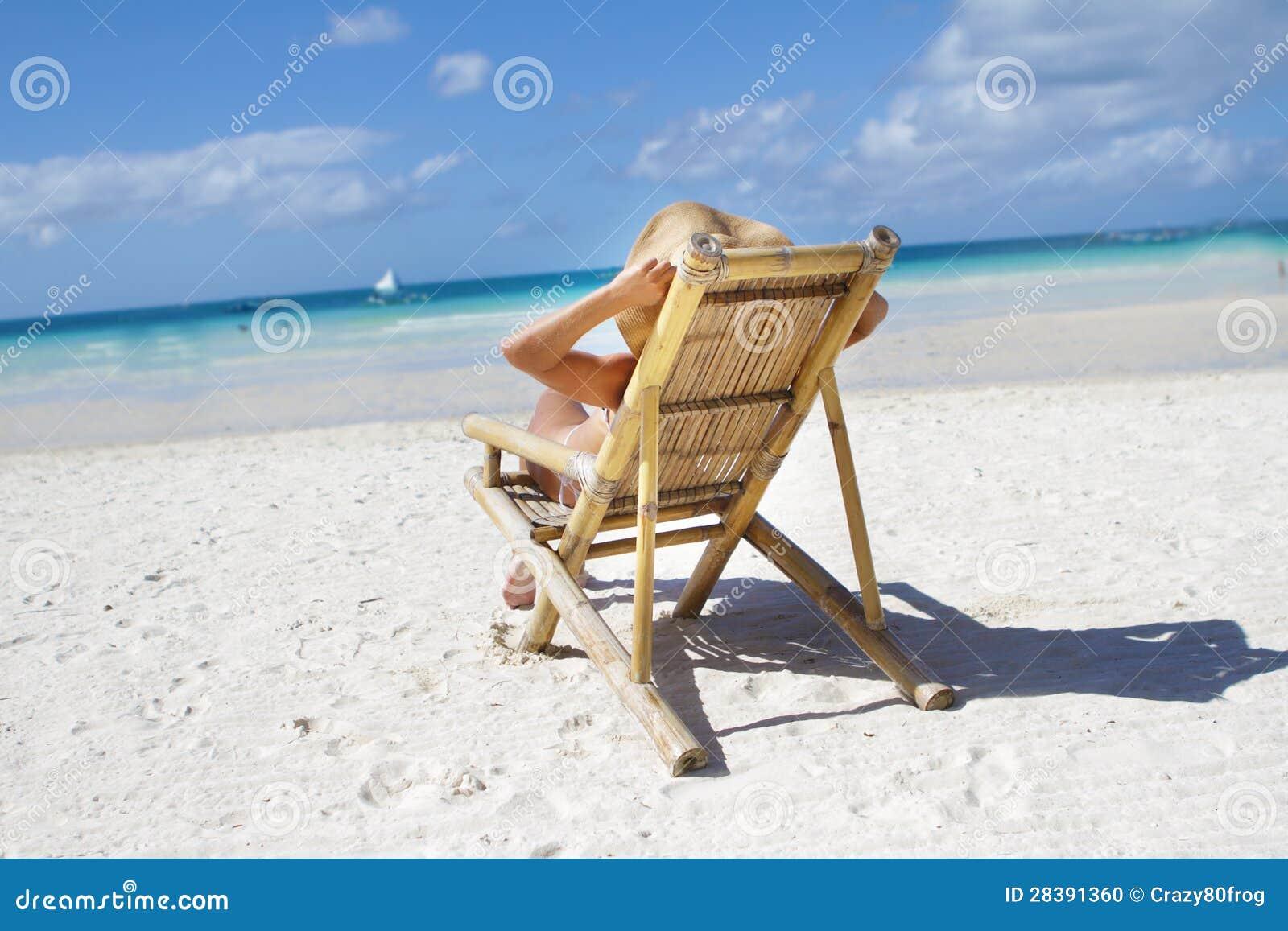 Sdraio Per La Spiaggia.Donna In Cappello Che Si Rilassa Sulla Spiaggia Su Uno Sdraio
