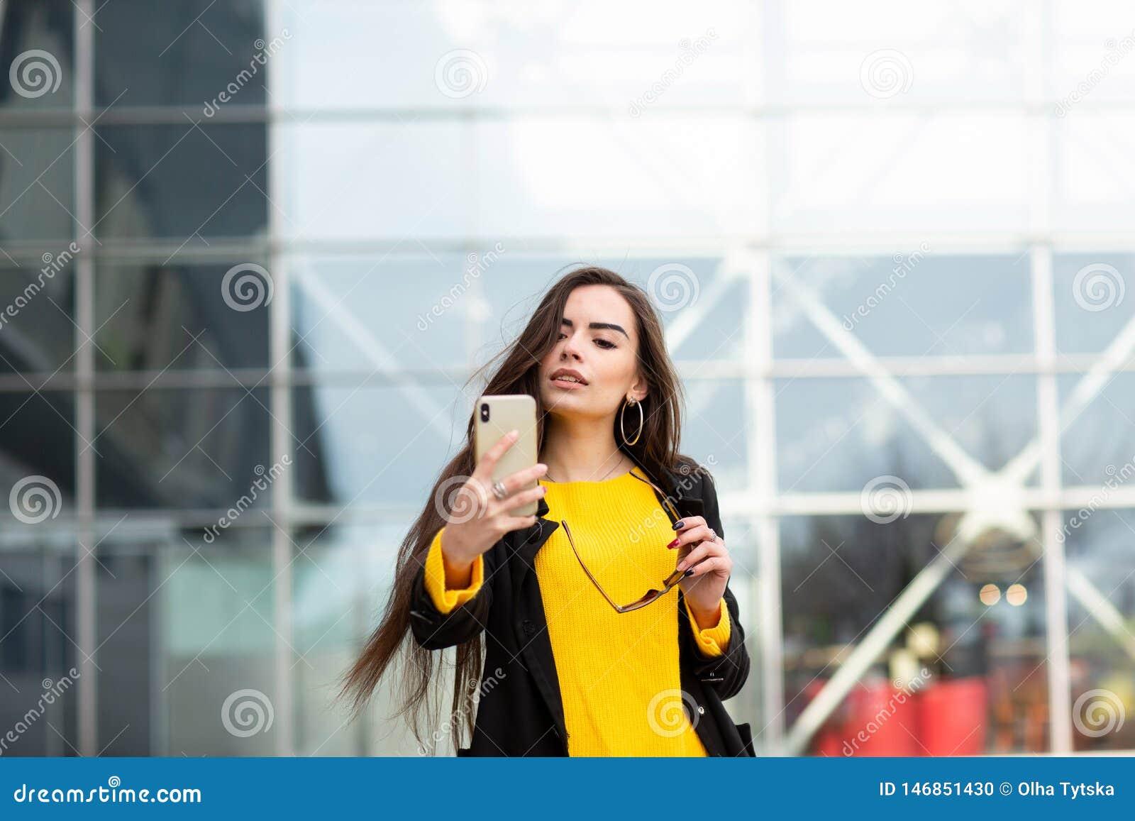 Donna castana allegra in maglione giallo che fa sefie contro il fondo dell aeroporto Tecnologia moderna