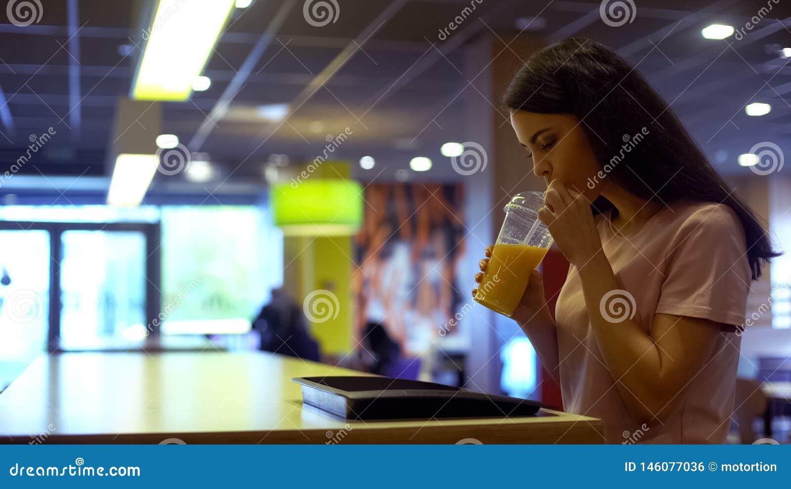 Donna castana che beve succo d arancia fresco da vetro di plastica, dieta antiossidante