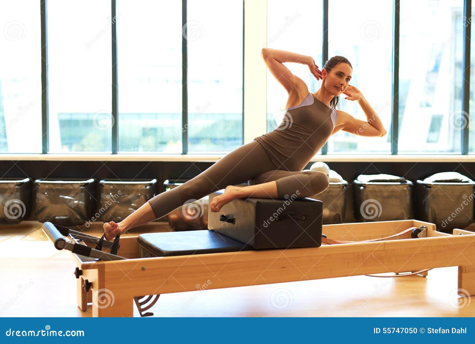 Donna castana che pratica Pilates in studio
