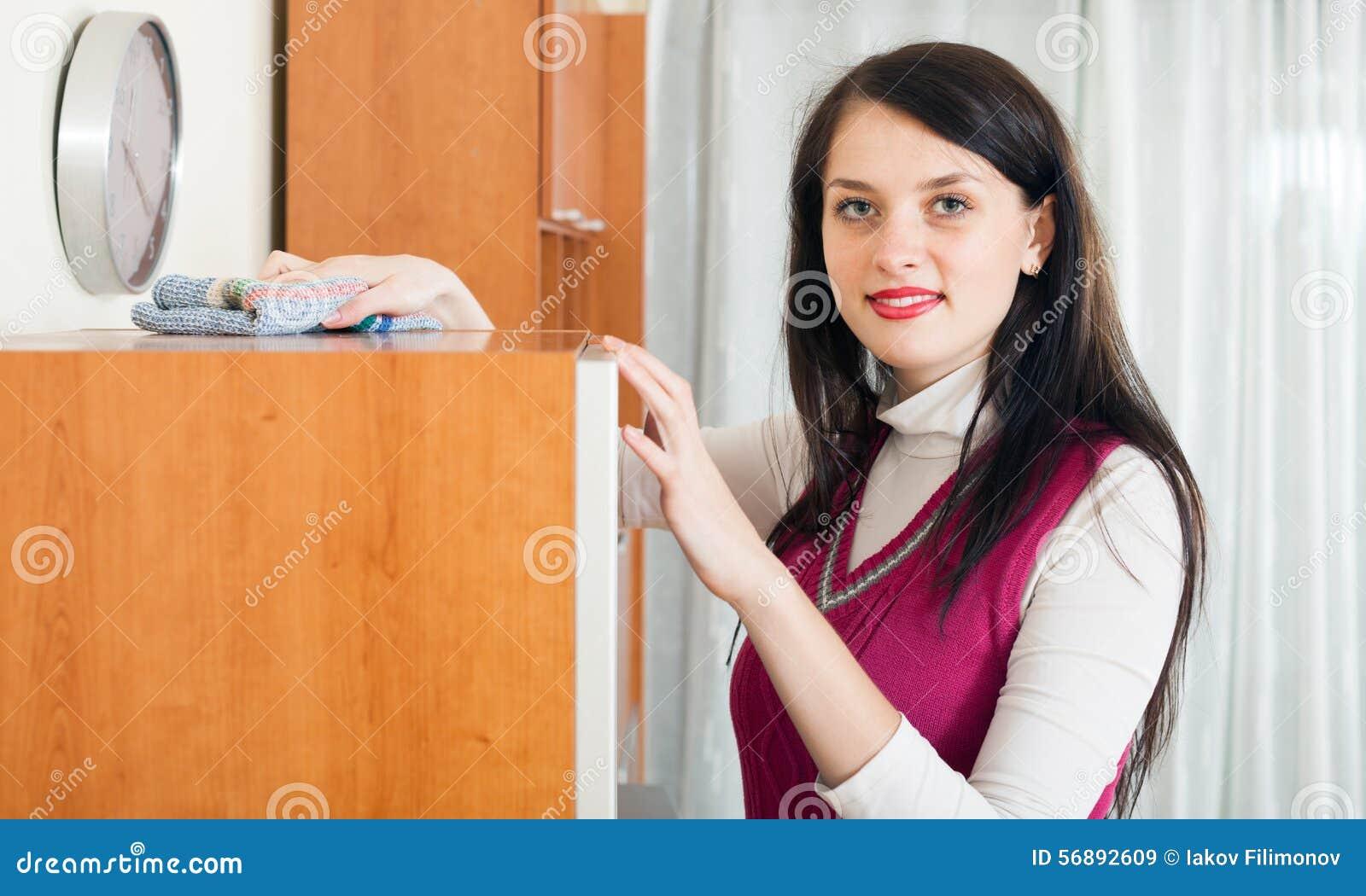 Donna castana che pulisce furiture di legno