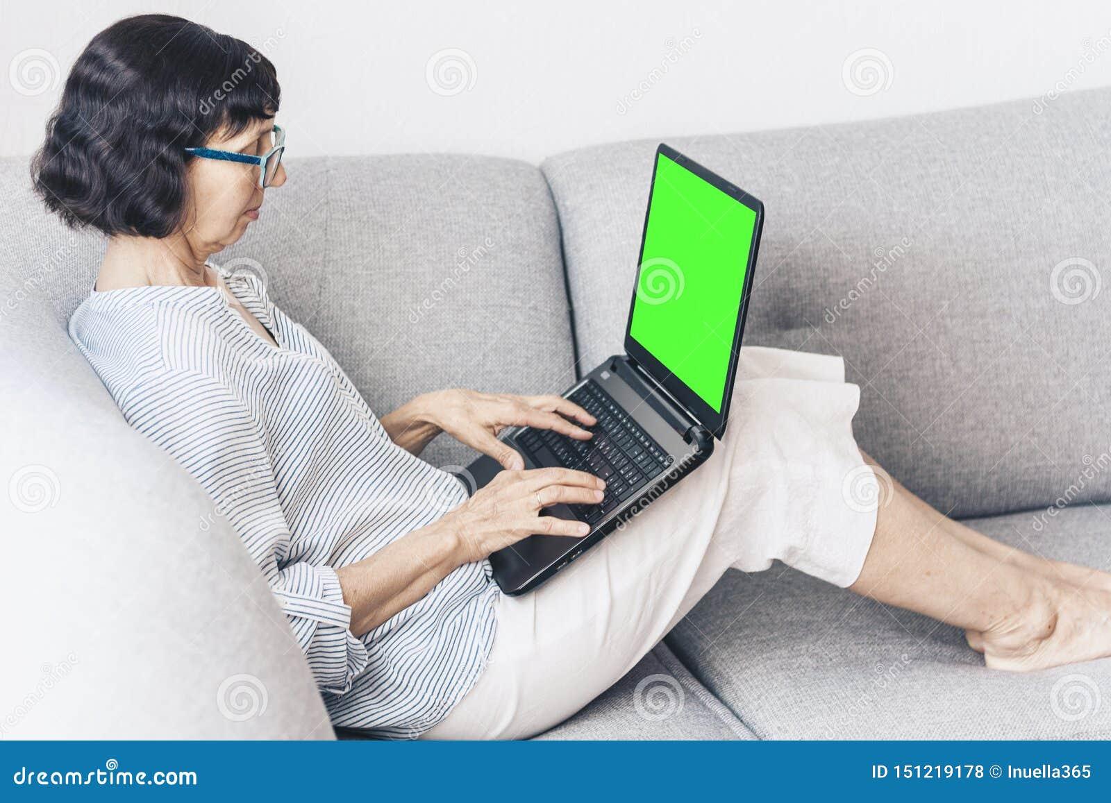 Donna castana di mezza età con i vetri sul funzionamento grigio del sofà sul computer portatile verde dello schermo, fuoco molle