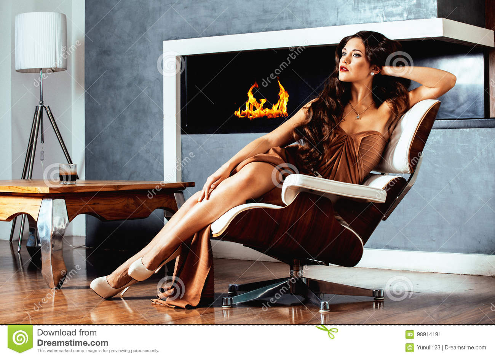 Donna castana di Yong di bellezza che si siede vicino al camino a casa