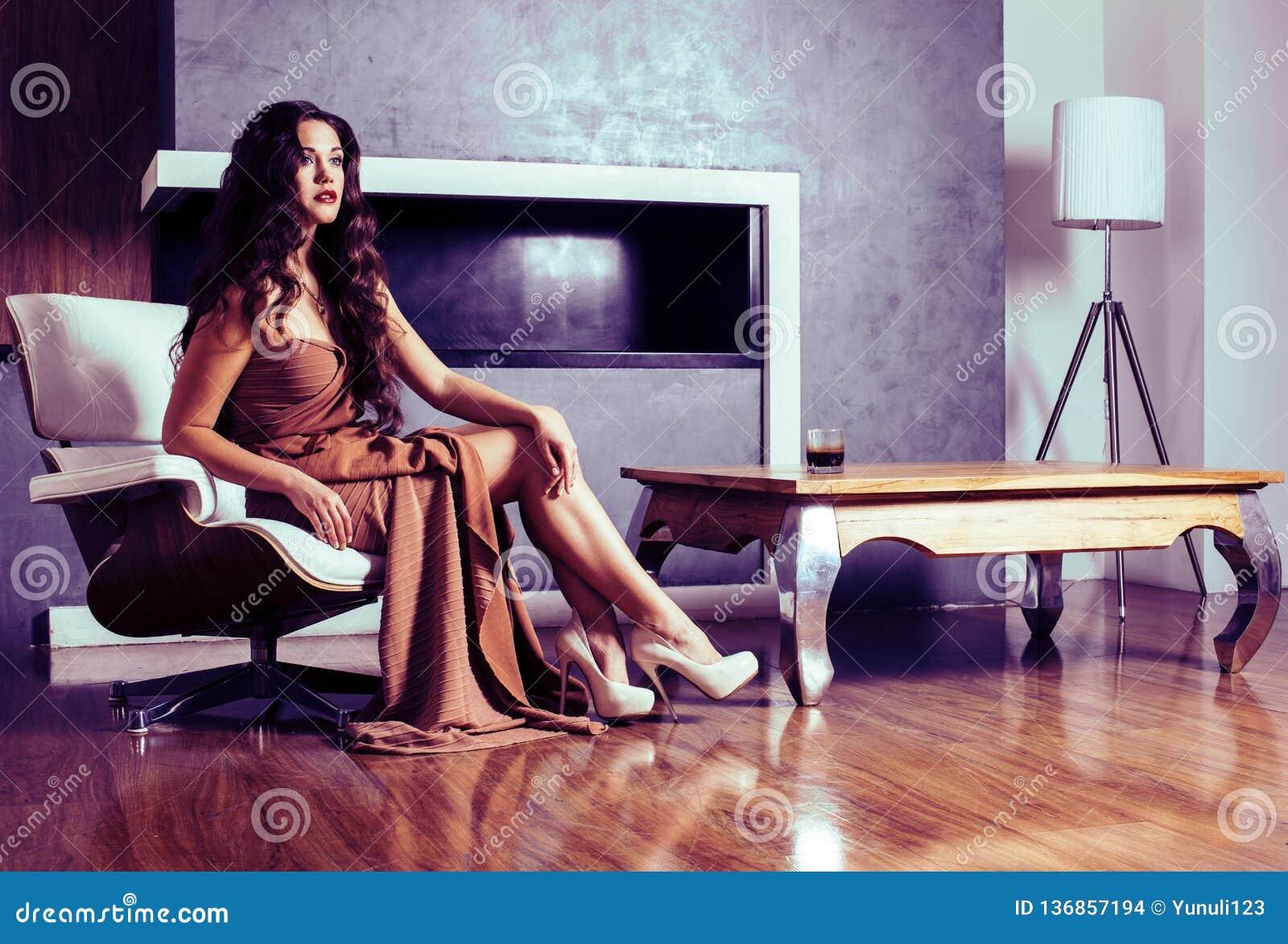 Donna castana di Yong di bellezza che si siede vicino al camino a casa, winte
