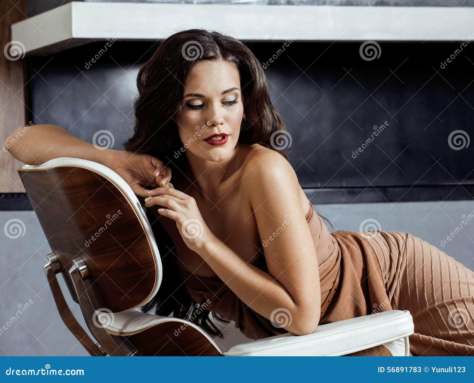 Donna castana di Yong di bellezza che si siede vicino al camino