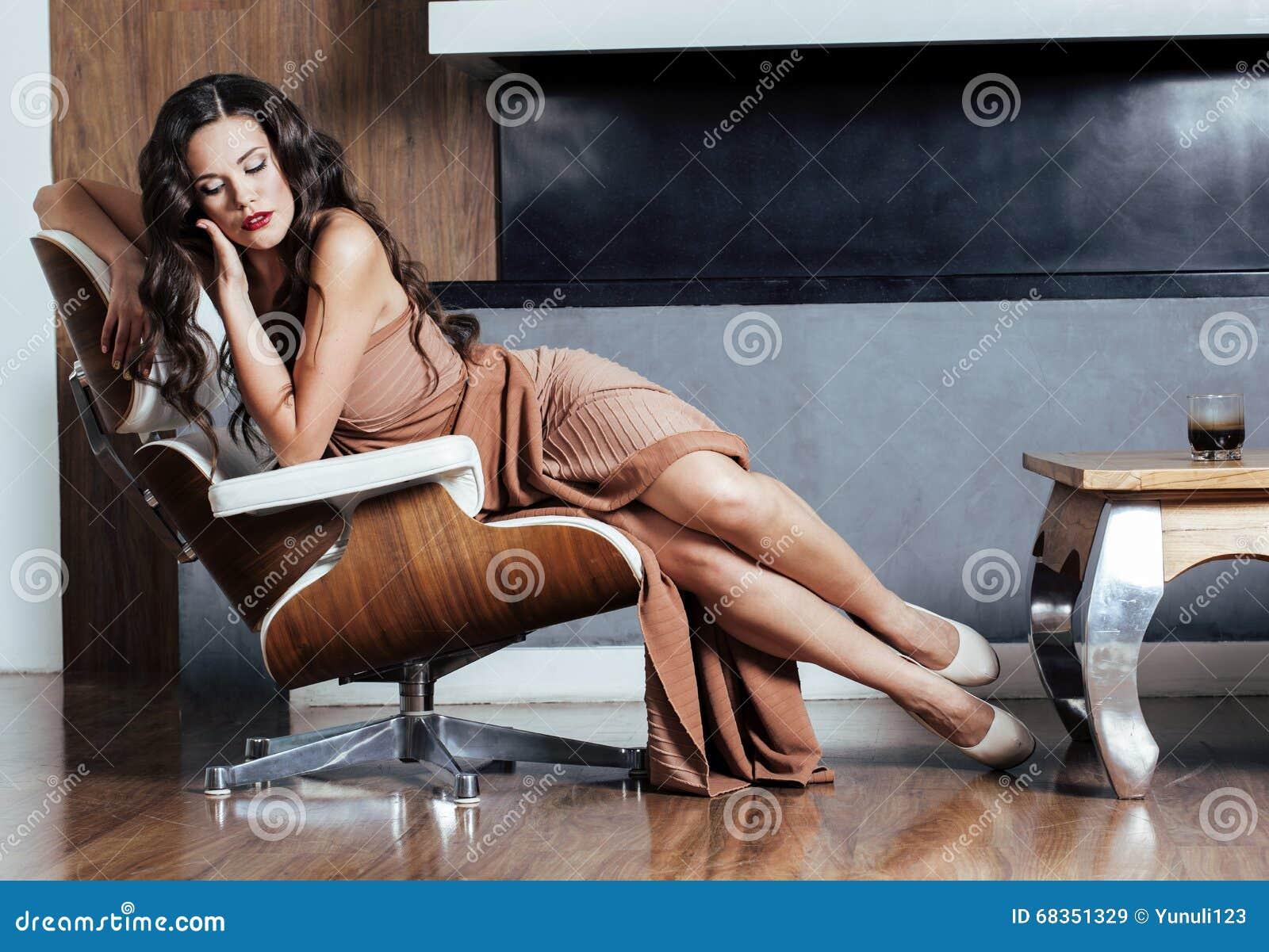 Donna castana di Yong di bellezza che si siede vicino al camino a casa, sera calda di inverno nell interno, aspettante per celebr