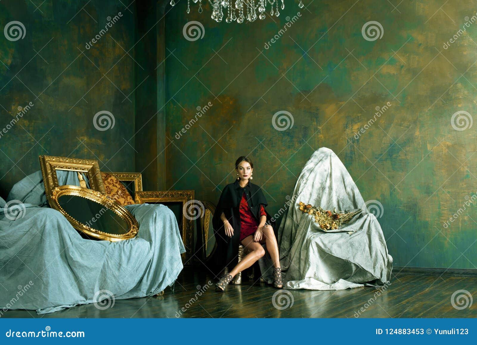 Donna castana ricca di bellezza nei telai vuoti vicini interni di lusso,