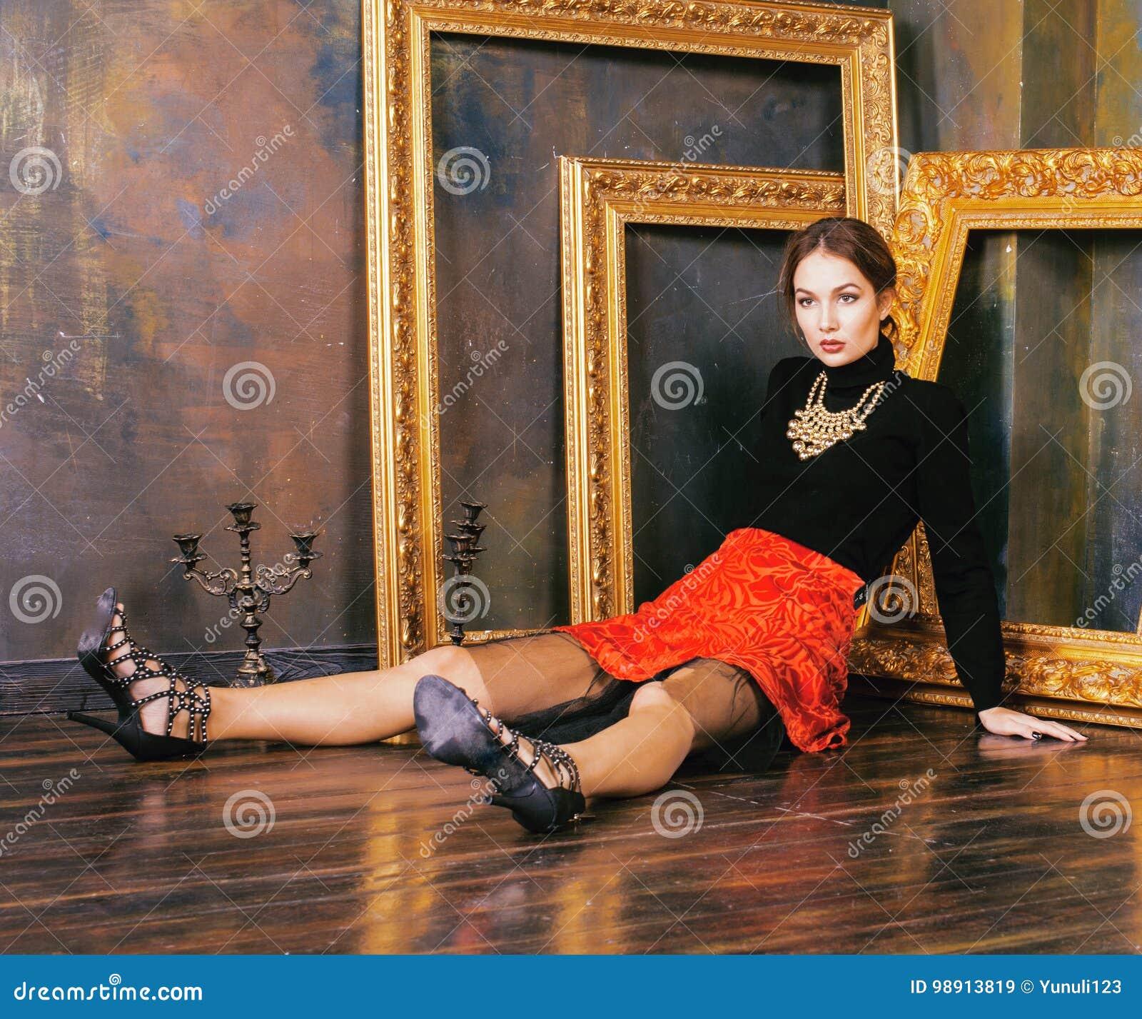 Donna castana ricca nei telai vuoti vicini interni di lusso, eleganza d annata di bellezza