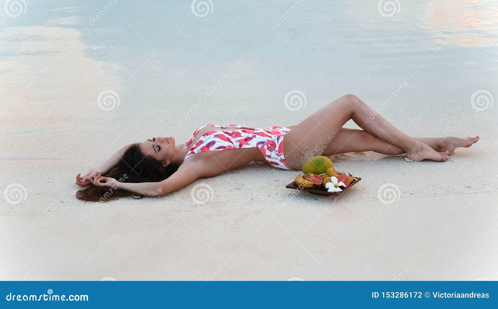 Donna castana spensierata che si trova sulla sabbia bianca che gode della vita sulla spiaggia tropicale Modello sexy del bikini c