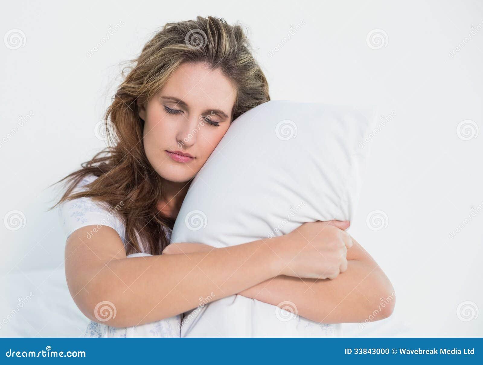Donna che abbraccia cuscino che si siede sul suo letto - Letto che si chiude ...