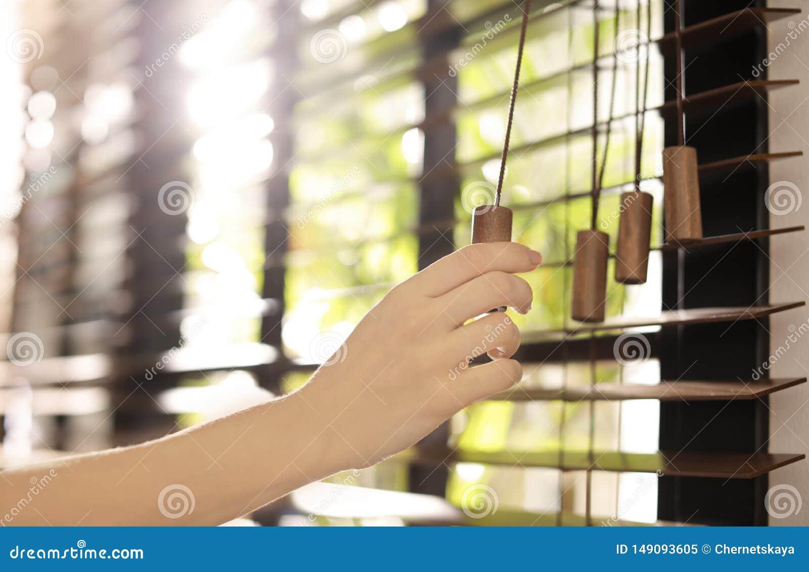 Donna che apre i ciechi di finestra orizzontali a casa
