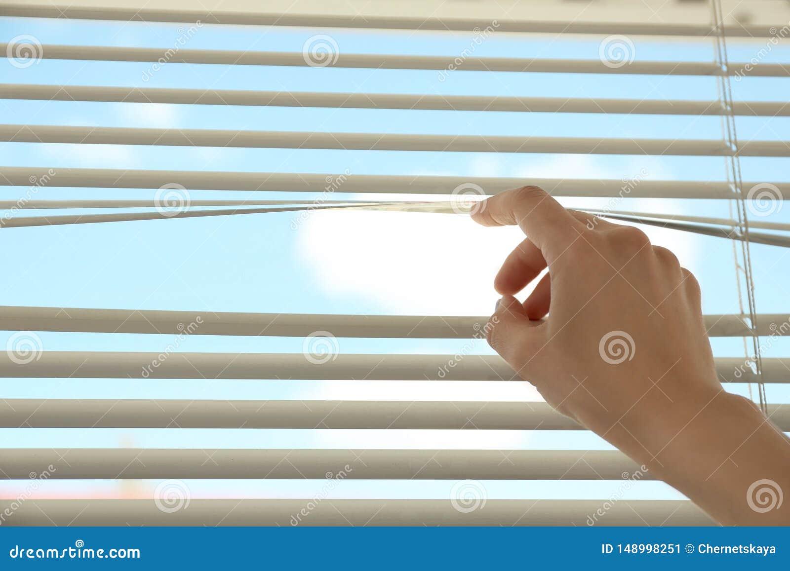 Donna che apre i ciechi di finestra orizzontali a casa, primo piano