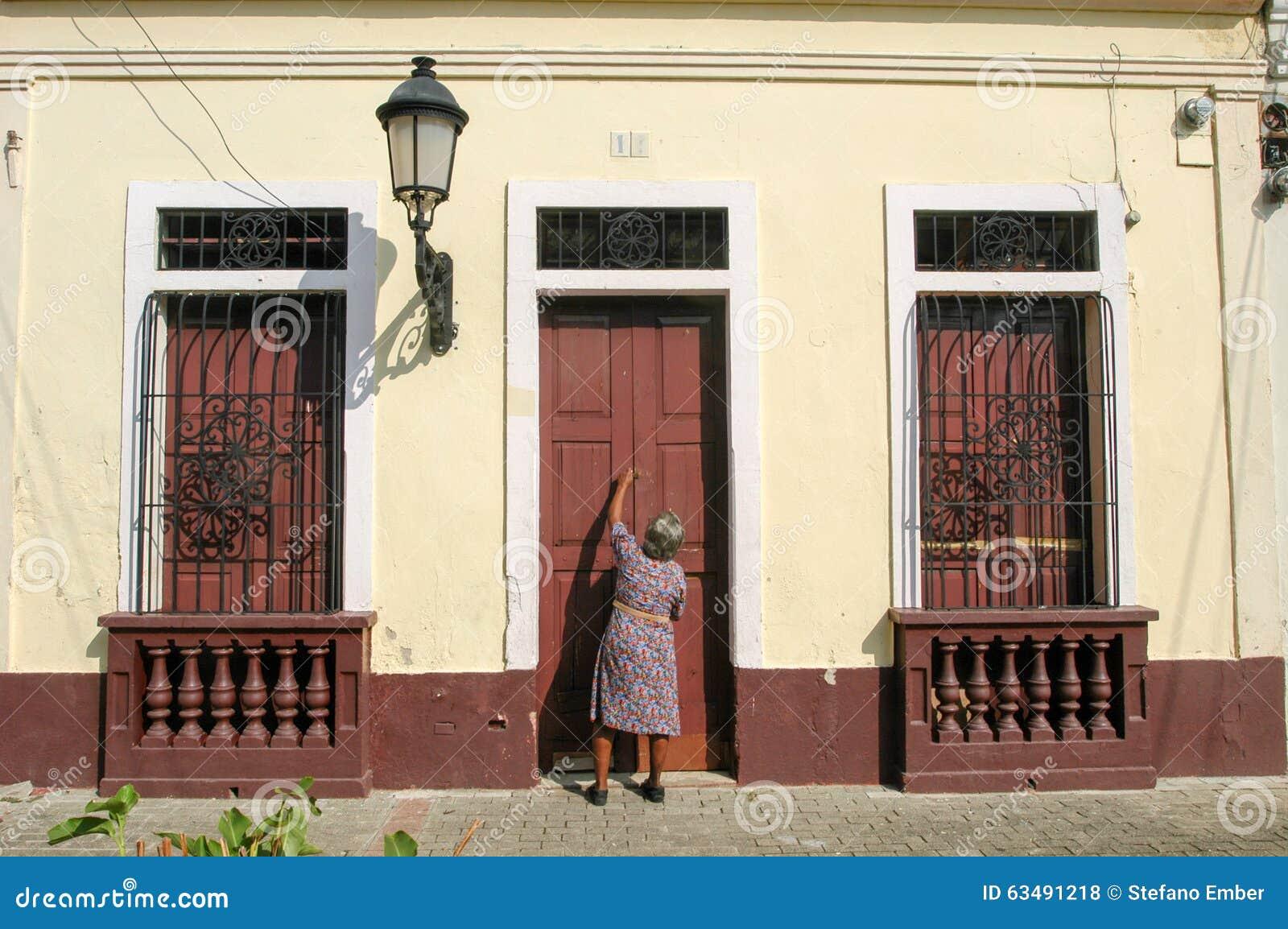 Donna che apre la porta di entrence della sua casa for Planimetrie della casa coloniale